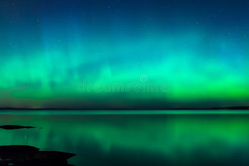Nordlichter über See in Finnland lizenzfreies stockbild