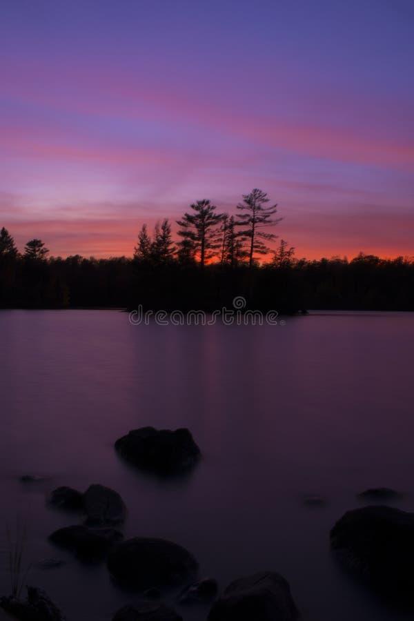 Nordlig solnedgång över sjön royaltyfria bilder