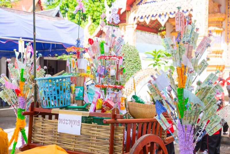 Nordlig thailändsk ritual för Tan Kuay Salak festival som folket ska ge livsmedel- och värdesaksaker till templet och munkarna arkivfoton