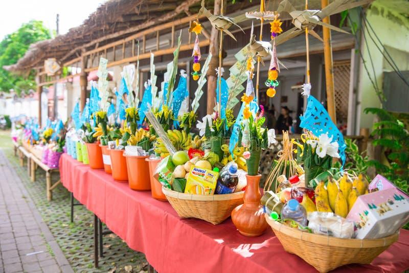 Nordlig thailändsk ritual för Tan Kuay Salak festival som folket ska ge livsmedel- och värdesaksaker till templet och munkarna arkivbilder