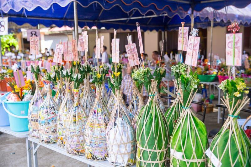 Nordlig thailändsk ritual för Tan Kuay Salak festival som folket ska ge livsmedel- och värdesaksaker till templet och munkarna arkivfoto
