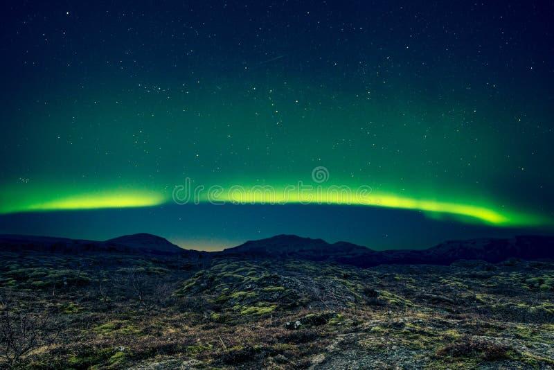 Nordliga ljus över avlägsna berg royaltyfria bilder