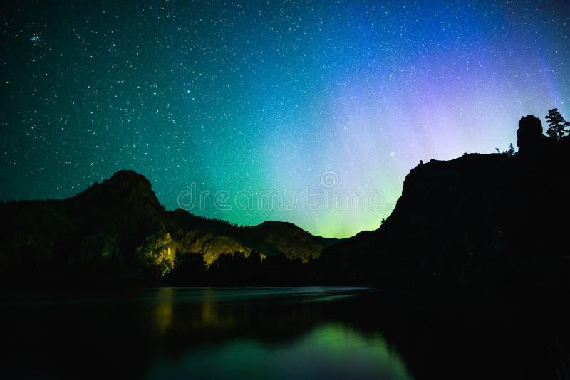 Nordliga ljus över berg och vatten royaltyfria foton