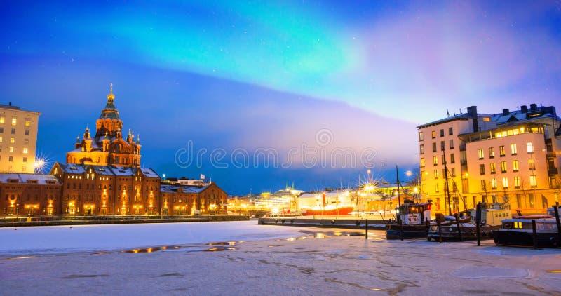 Nordliga ljus över den djupfrysta gamla porten i det Katajanokka området med Uspenski den ortodoxa domkyrkan i Helsingfors Finlan royaltyfri bild