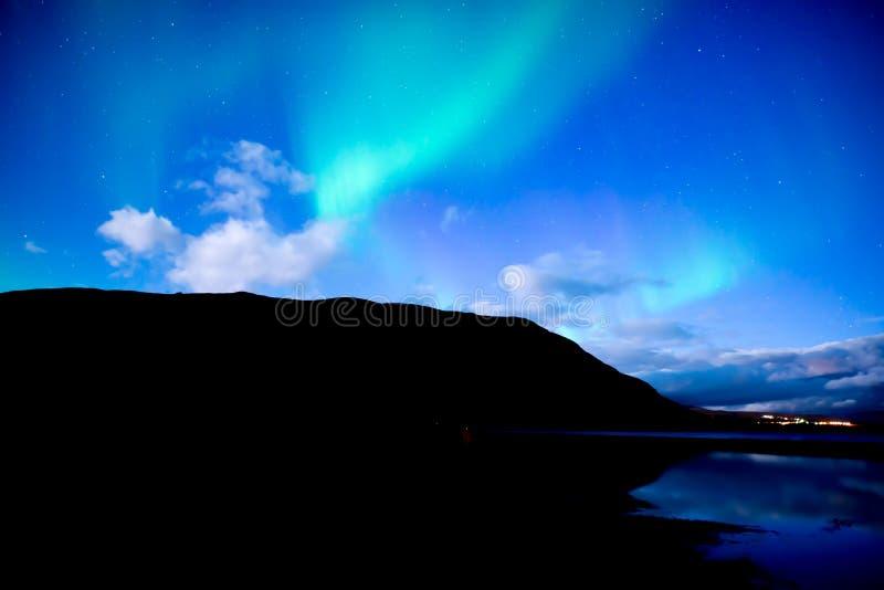 Nordliga ljus som dansar över lugna sjönorrsken arkivfoto