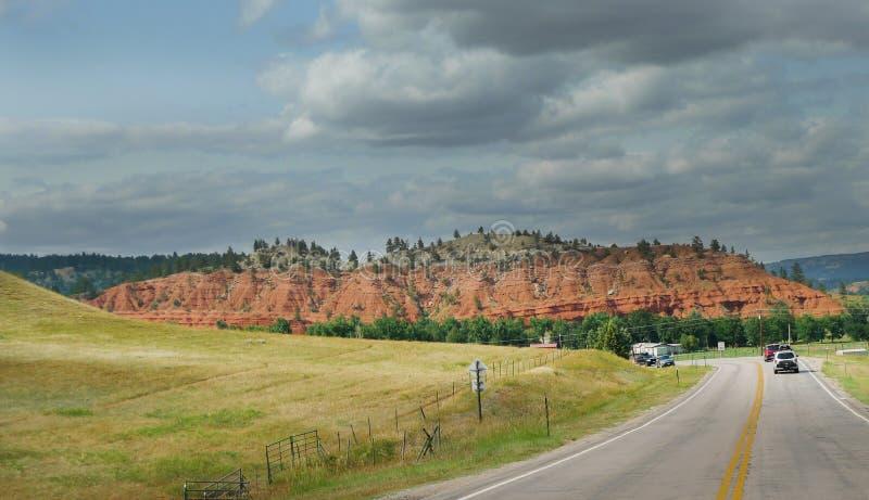 Nordostliga Wyoming nära torn för Devi ` s med rött vaggar kullar och buktiga vägar royaltyfri bild