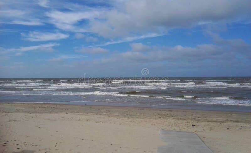 Nordsjökust med en molnig himmel och några havsvågor fotografering för bildbyråer