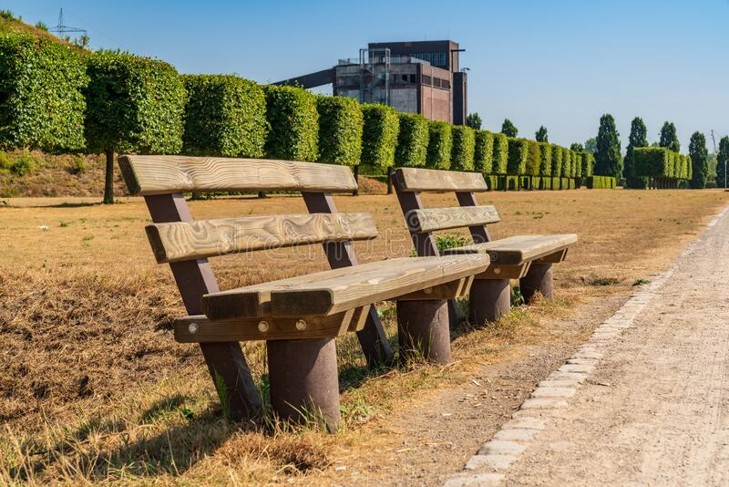 Nordsternpark, Gelsenkirchen, North Rhine-Westfalia, Germany. Benches near a parched meadow, with the ruin of an old coal bunker in the background, seen in the royalty free stock photo