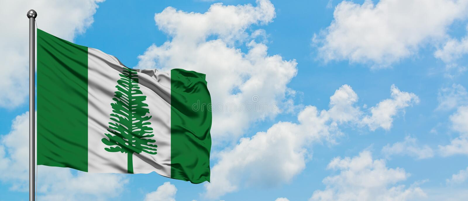 Norfolk Island flag waving in the wind against white cloudy blue sky. Diplomacy concept, international relations.  stock photos