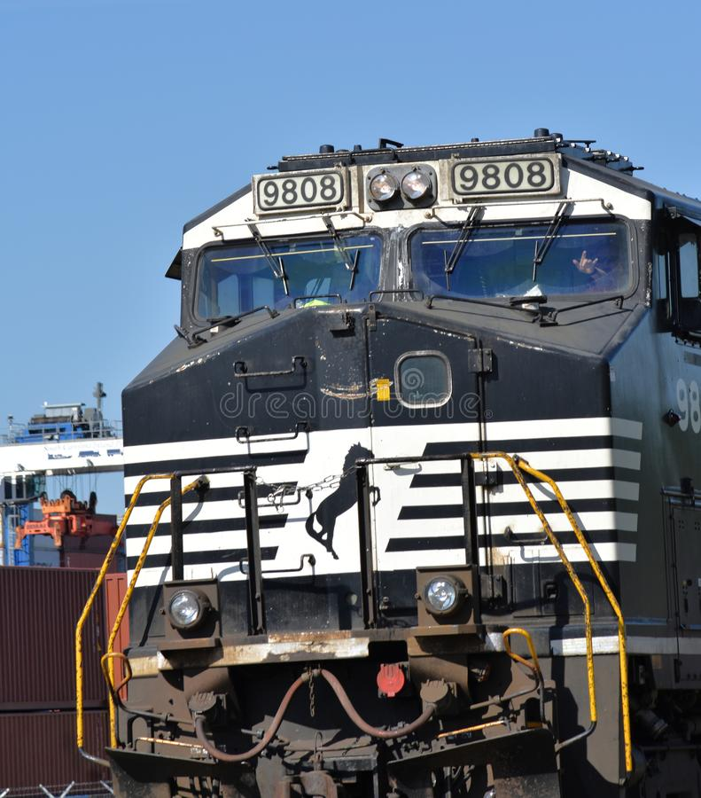 Norfolk Southern locomotive 9808. Pulls a train of intermodal freight east towards Charleston near Greer. The engineer waves from the cab. A gantry crane at royalty free stock photo