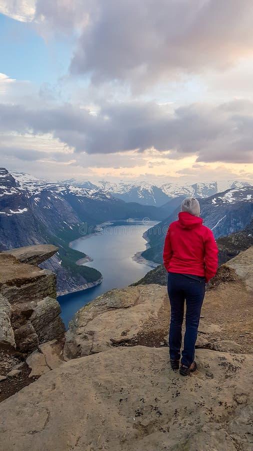 Norge - flickaanseende bredvid Trolltunga under soluppg?ngen arkivbild