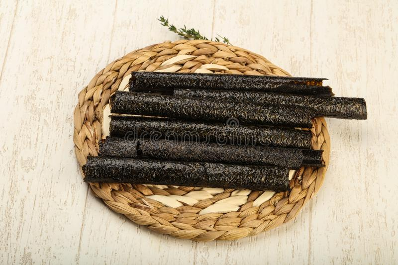 Nori chips. Asian cuisine - Nori chips over the wooden background royalty free stock photography