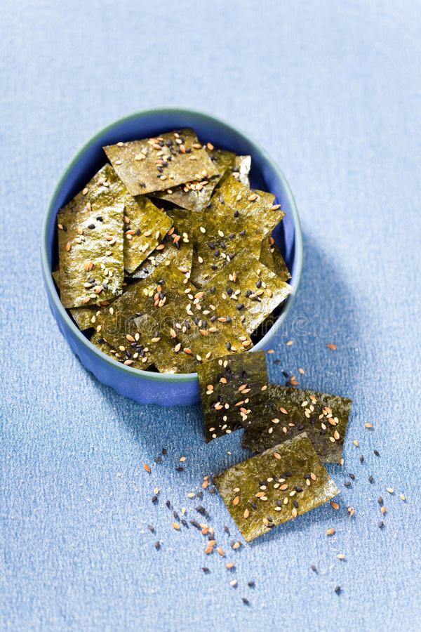 Nori chips. With sea salt, sesame seeds and flax seeds, selective focus royalty free stock photo