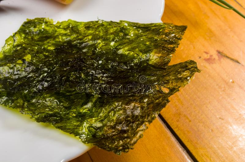 nori chips on a white ceramic plate, seaweed sheets stock photos