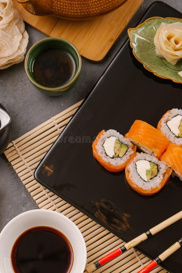 Nori Maki Philadelphia Sushi Rolls Set med den rå laxen och gräddost på svart stentabellbakgrund med stället för text arkivfoton