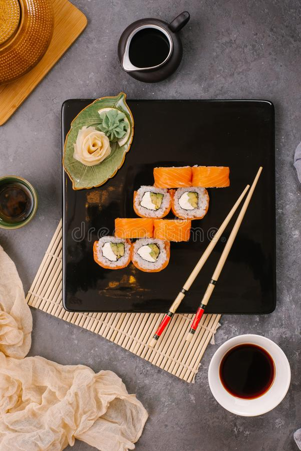 Nori Maki Philadelphia Sushi Rolls Set with Raw Salmon and Cream Cheese on Black Stone Table Background with Place for Text. royalty free stock images