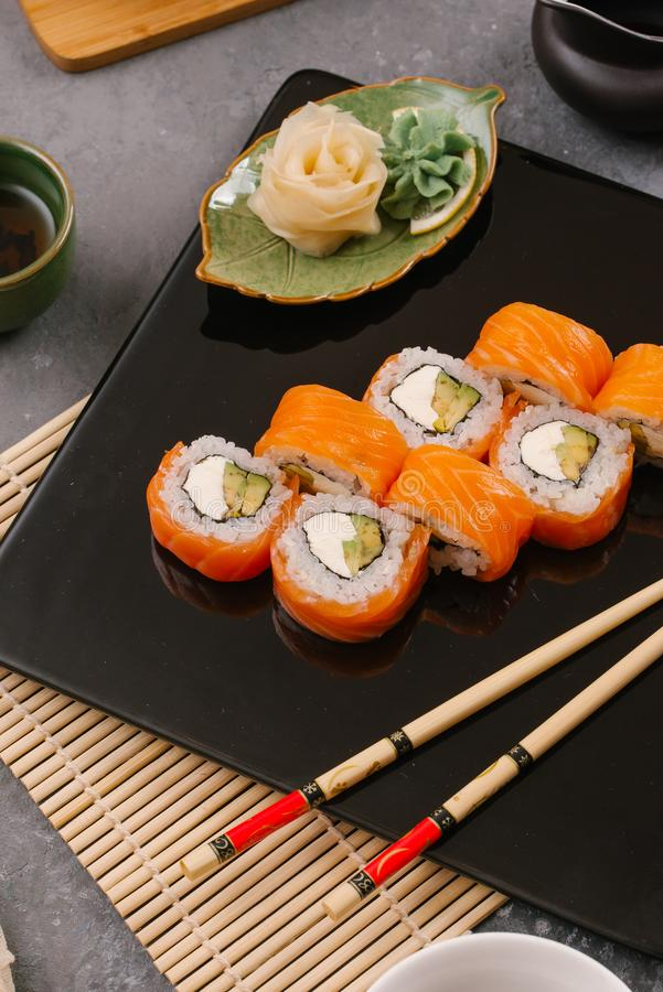 Nori Maki Philadelphia Sushi Rolls Set with Raw Salmon and Cream Cheese on Black Stone Table Background with Place for Text. stock photos