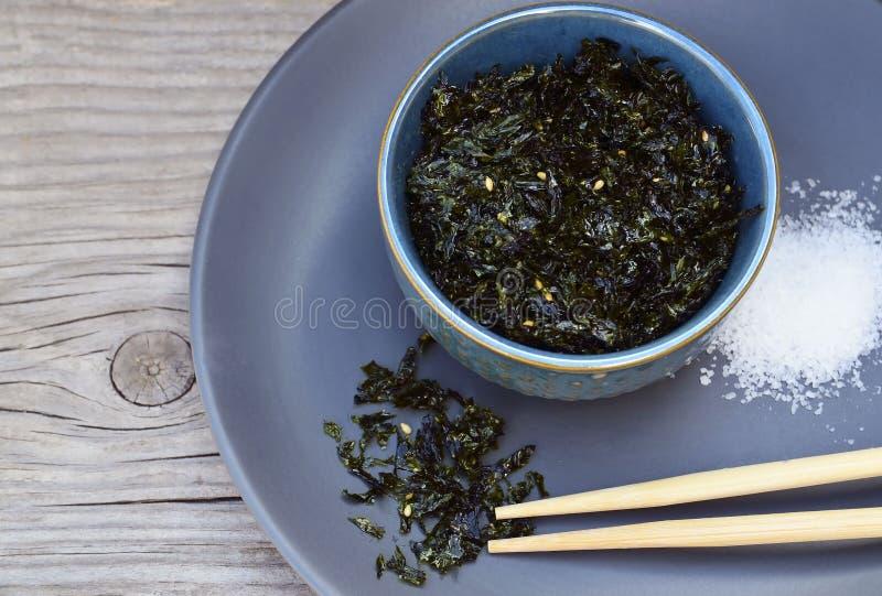 Nori secado roasted salgado da alga com sementes de sésamo em uma bacia azul na tabela de madeira velha Petisco saudável, conceit foto de stock
