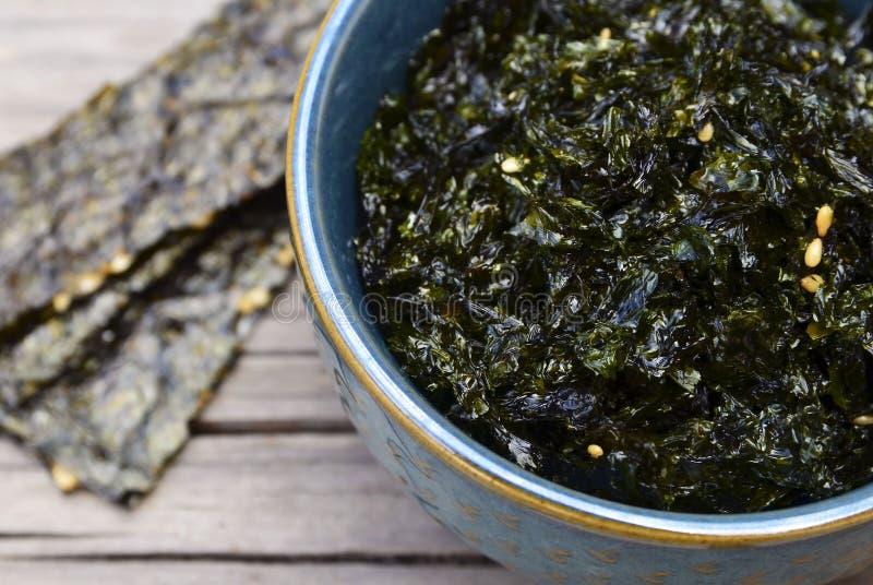 Nori secado roasted salgado da alga com sementes de sésamo em uma bacia azul na tabela de madeira velha Petisco saudável, conceit foto de stock royalty free