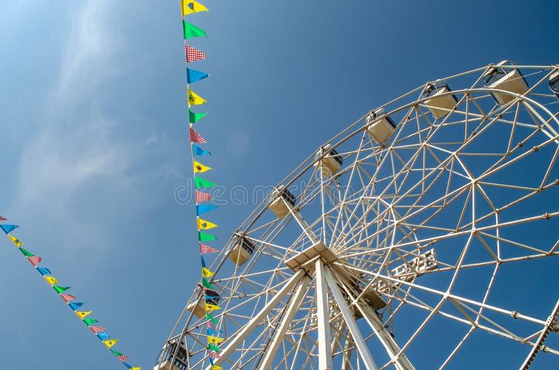 Noria y banderas coloridas en fondo del cielo azul fotografía de archivo