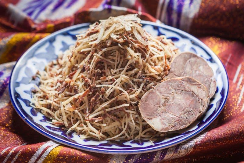 Norin national de nourriture d'Ouzbékistan sur des adras traditionnels de tissu images stock