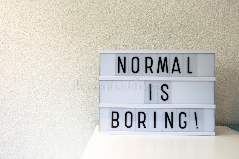 Normal is boring written in Light box home decoration, motivational sign retro home, space for text stock images