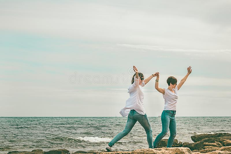 Normal girls on the beach with their arms up royalty free stock photo
