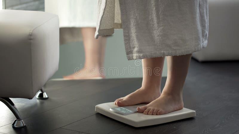 Normal vikt, flicka som kontrollerar banta resultat på våg hemma, sund kropp fotografering för bildbyråer