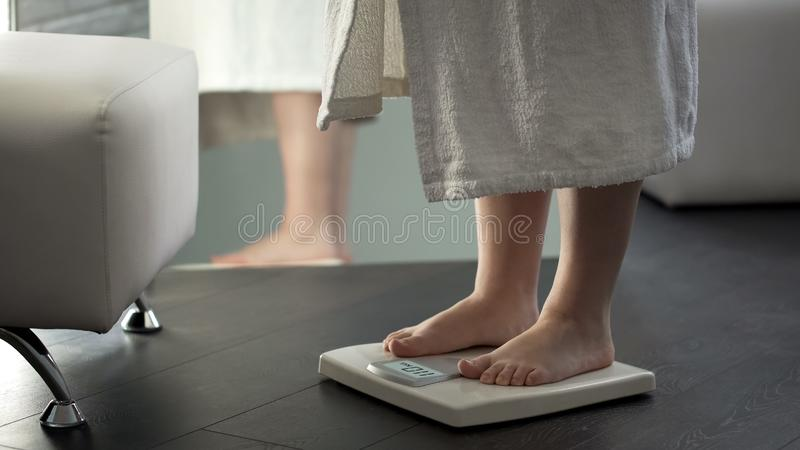 Normal weight, girl checking dieting results on scales at home, healthy body. Stock photo stock image