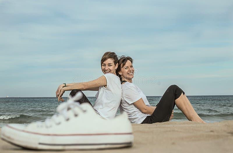 Normalne kobiety na plażowy ono uśmiecha się i siedzieć na piasku zdjęcie stock