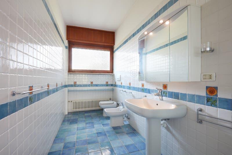 Normalt badrum med blåa och vita tegelplattor i lägenhetinre arkivbild