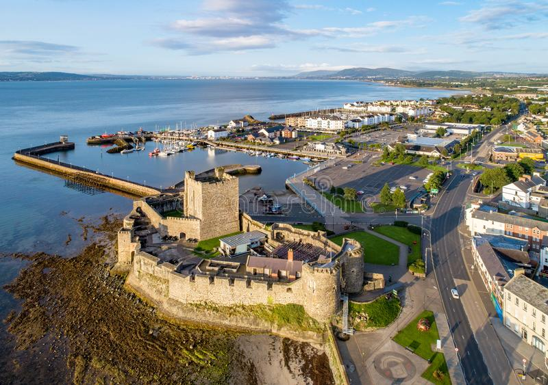 Norman castle in Carrickfergus near Belfast. Belfast Lough. Medieval Norman Castle in Carrickfergus in sunrise light. Aerial view with marina, yachts, parking royalty free stock image