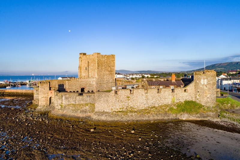 Norman castle in Carrickfergus near Belfast. Medieval Norman Castle in Carrickfergus near Belfast in sunrise light. Aerial view with marina, yachts and far view royalty free stock image