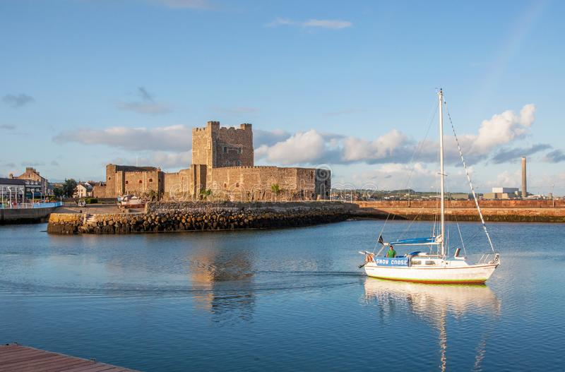 Normandisk slott och yacht i Carrickfergus nära Belfast arkivbild