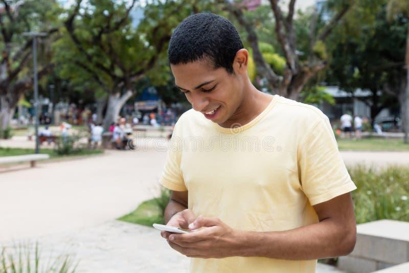 Norr afrikansk man som överför meddelandet med telefonen royaltyfri foto