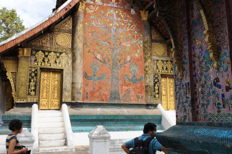 Norr Laos: Turist- besöka den Wat Xieng Thong templet i den Luang Brabang staden arkivfoton
