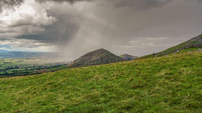 Norr Pennineslandskap med ett regnmoln ?ver den Dufton piken royaltyfria foton