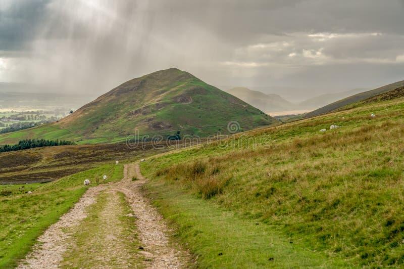 Norr Pennineslandskap med ett regnmoln ?ver den Dufton piken fotografering för bildbyråer