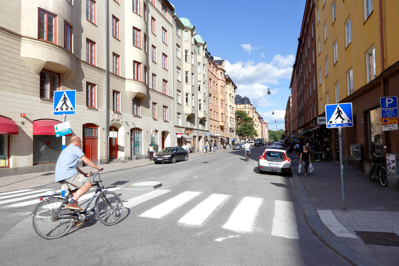 Norrbackagatan with cyclist. Stockholm, Sweden - June 27, 2016: A cyclist turns into the street Norrbackagatan from the street Rorstrandsgatan in the Vasastaden royalty free stock photography