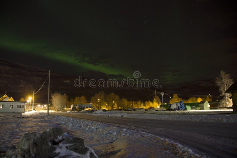 Norrskenet för nordliga ljus som stiger bak ett berg i en liten by i norden av Norge I mitt av vintern arkivbild