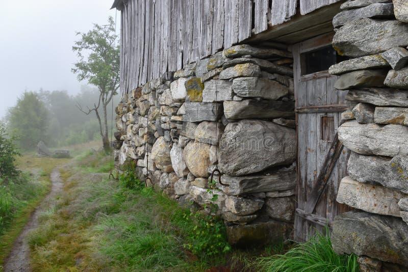 Norsk berglantgård på den dimmiga morgonen arkivbild