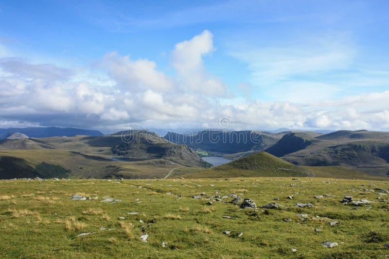 Norsk sjö, kullar och grön dal, molnig himmel royaltyfri foto
