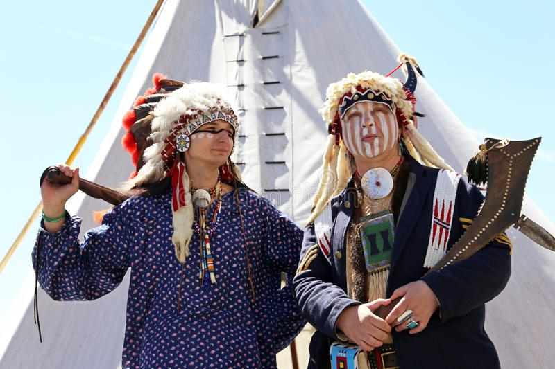 North American Indians stand with weapon near a wigwam royalty free stock images
