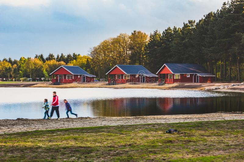 NORTH BRABANT - NETHERLANDS - April, 26, 2017: three children playing on along the beach of pond. Rest and recreation in royalty free stock photo