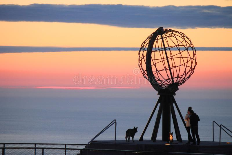 The North Cape, with people and dogs. Midnight sun seen from the North Cape, the northernmost promontory of Europe Norway, region of Finnmark Arctic Circle royalty free stock image