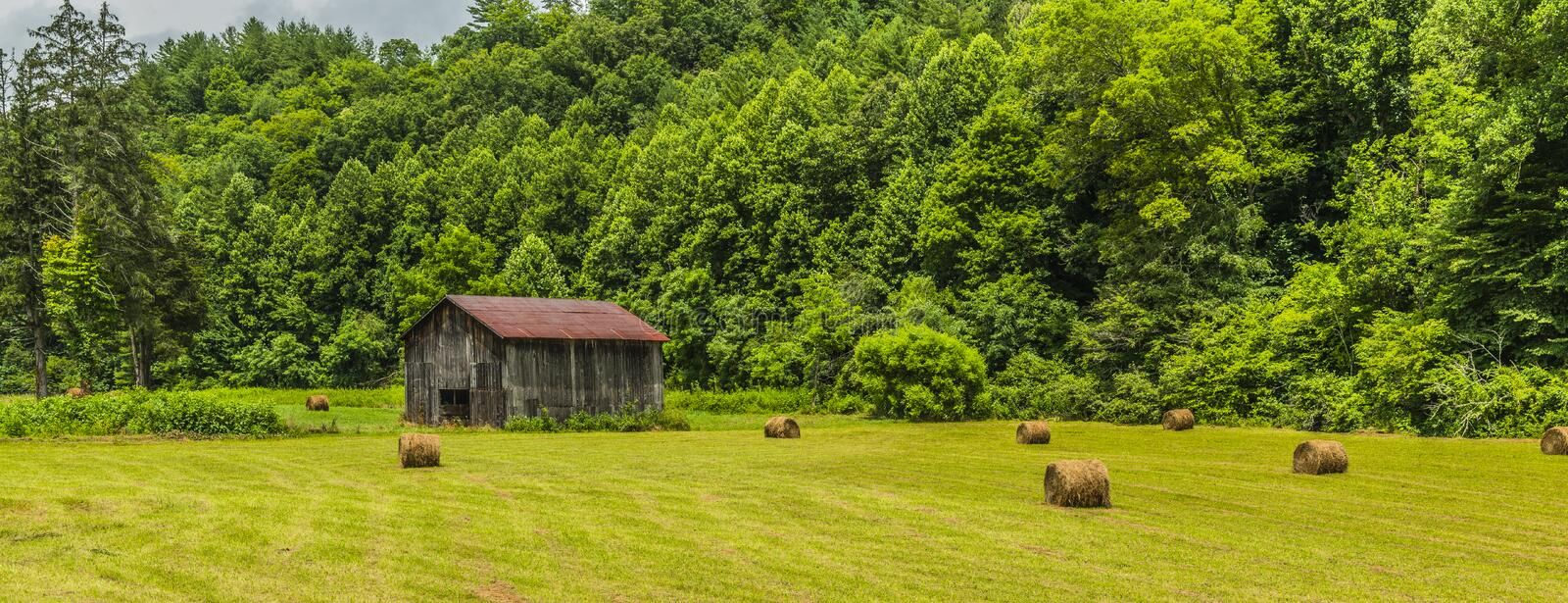 North Carolina Barn With Round Bales in Field 1 stock images