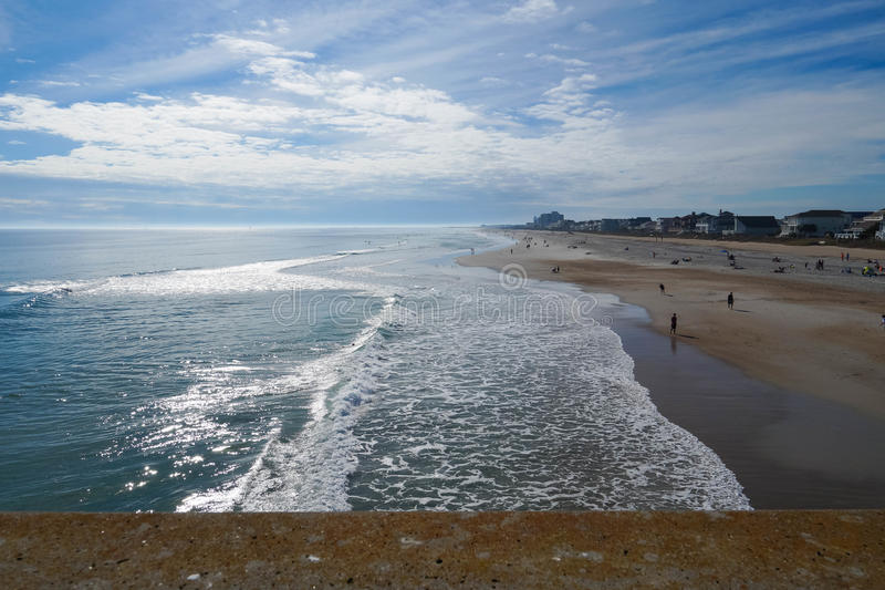 North Carolina beach. Luminous seas and surf spray on Wrightsville Beach at low tide on a sunny day and high white clouds. This a view from above seen from royalty free stock photos