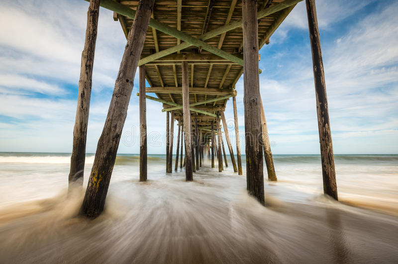 North Carolina Outer Banks Beach Seascape Nags Head OBX NC. Featuring ocean waves crashing into an old fishing pier on the beach royalty free stock image
