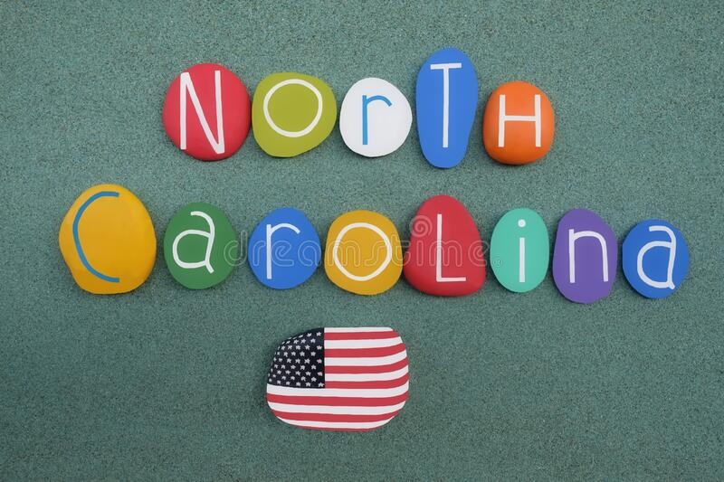 North Carolina, United States of America, souvenir with a multi colored stone letters composition over green sand. Souvenir of North Carolina, United States of royalty free stock photo