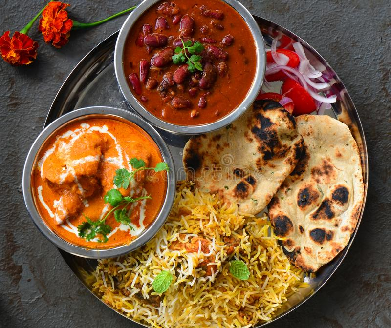 North Indian party meal-Punjabi non vegetarian thali. Indian thaali meal with butter chicken,rajma masala,chicken biryani,Tandoori Roti and salad stock photo